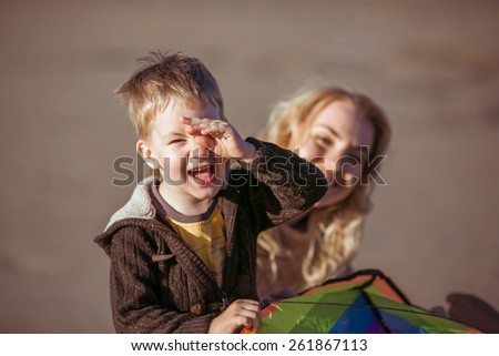 A five-year-old boy is smiling for the camera, closing his left eye with the left hand and holding a kite in the right hand. His mom is peeking out from behind his back. Clothes: casual. - stock photo