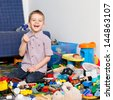 A five year old child playing in his room with a lot of toys around him. A five year old boy holding something in his small fist and laughing - stock photo