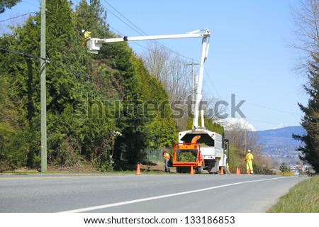 A flag person stands at the crest of a hill while a crew trims trees/Traffic Safety/A flag person stands at the crest of a hill while a crew trims trees - stock photo