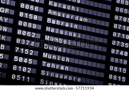 A flight schedule at the airport show Karachi, Amsterdam, Bahrain, Helsinki, Mumbai, Dubai, Munich, Tehran, Singapore - stock photo