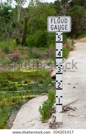 A flood gauge on a cement bridge crossing a creek in rural Texas - stock photo