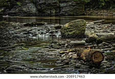 A flowing stream with log and rocks. - stock photo