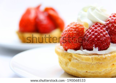 A fluffy pastry dessert topped with whip cream and fresh strawberries. - stock photo