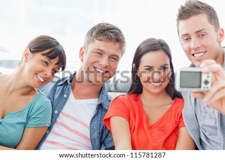 A focused shot on the group sitting and posing for a camera photo - stock photo
