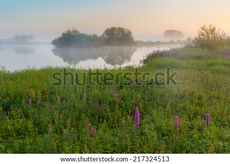 A foggy sunrise on a beautiful morning in early autumn - stock photo