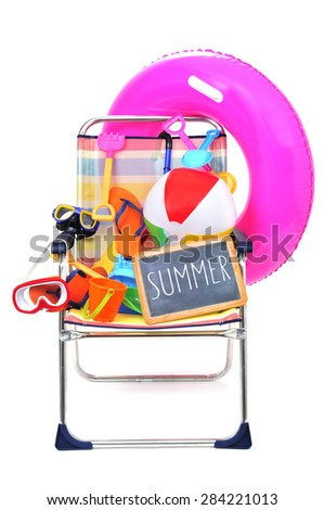 a foldable beach chair full of beach items, such as diving masks, pails and shovels, a beach ball or a swim ring, and a chalkboard with the word summer written in it on a white background - stock photo