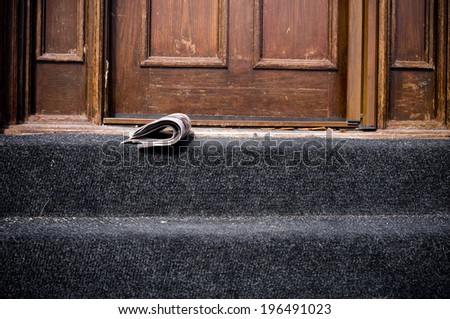 A folded newspaper sitting on a front stoop. - stock photo