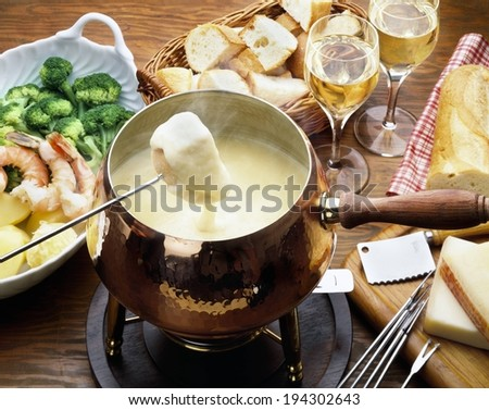 A fondue pot containing a melted substance and a cube of bread. - stock photo