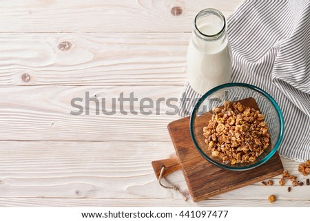 A food background with a glass bowl of cereal breakfast, milk or yogurt bottle and striped table cloth. Wooden background, top view. - stock photo