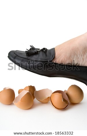 A foot ready to step on some brown eggshells. - stock photo