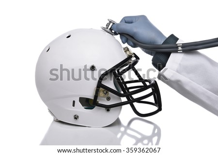 A football helmet and doctors hand holding a stethoscope on the crown of the helmet. Sports Concussion Concept, and related conditions, CTE, Alzheimer's, Parkinson's. - stock photo