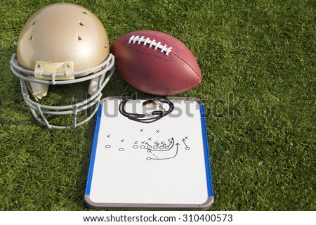 A football helmet, ball and clipboard with a play drawn on it. - stock photo