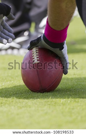 A football player setting up to snap the ball during a game. - stock photo
