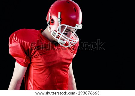 A football player taking his helmet on her head with blac background - stock photo