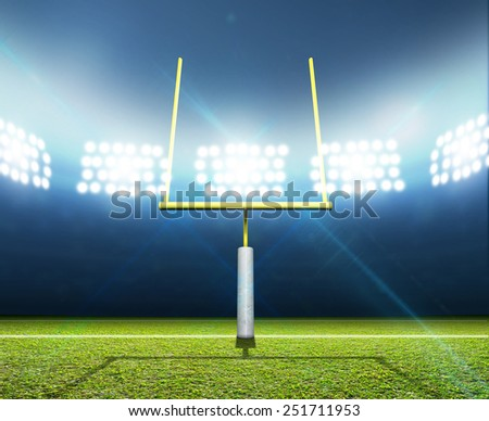 A football stadium with posts on a marked green grass pitch in the night time illuminated by an array of spotlights - stock photo