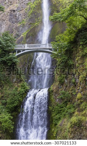 A footbridge arches over Multnomah Falls, on of the tallest waterfalls in the U.S., near Portland, Oregon - stock photo