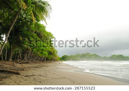 A foreboding sky at the surfing beach of Playa Dominicalito in Costa Rica - stock photo