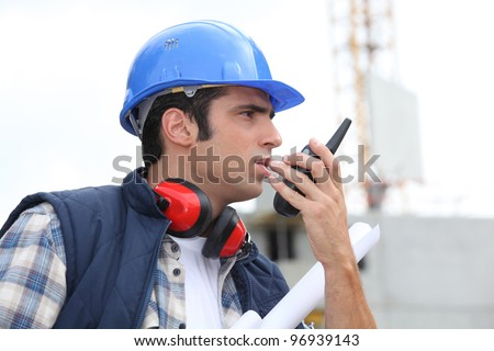 A foreman giving instructions through his cb. - stock photo