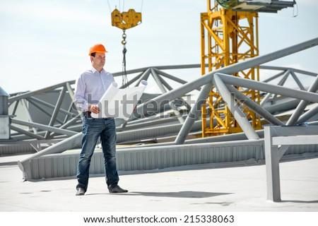 A foreman with drawings supervising the project at the construction. - stock photo