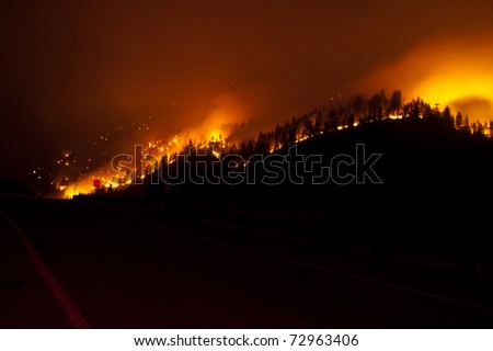 A forest fire burns at night alongside an interstate highway in western Montana.  Seen - stock photo