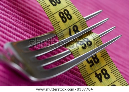 a fork and a measure tape, conceptual loose weight (soft and selective focus) - stock photo