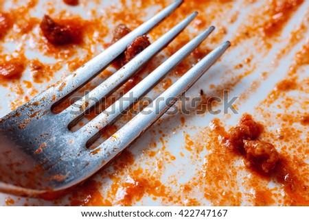 A fork on an empty used white plate with remains of tomato sauce - stock photo