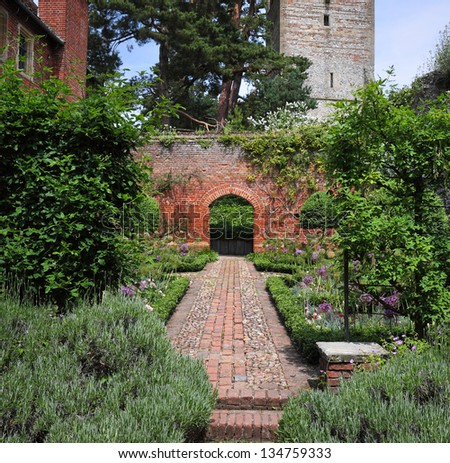 A Formal english Walled garden with path and archway - stock photo