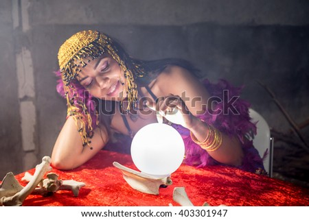 A fortuneteller loving her crystal ball with smoke around her. - stock photo