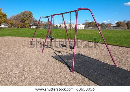a four swing swingset at a playground / park - stock photo