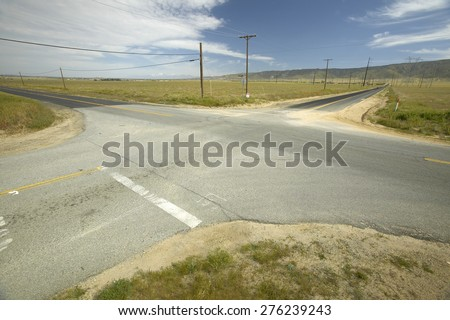 A four way intersection of four roads in the desert near Lancaster, CA - stock photo