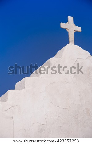 A fragment of a white church with a cross on a background of blue sky. Greece. - stock photo