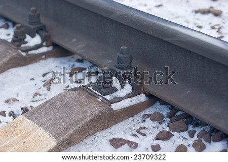 A fragment of an old rusty rail covered with snow - stock photo