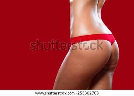A fragment of woman body in red panties / Lingerie / Underwear/Woman body shape/Female body/Woman body - stock photo