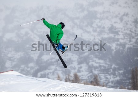 A free-ride ski jumper, with skis crossed against a mountains - stock photo