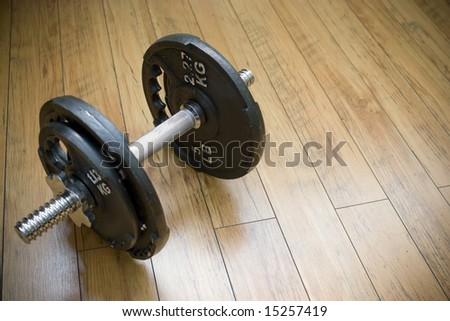 A free weight dumbell sitting on a wood floor - the perfect accessory to any home gym. - stock photo