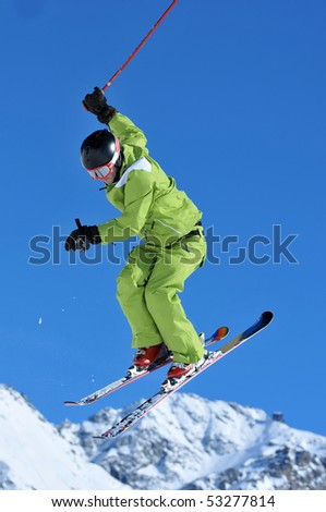 a freestyle ski jumper in green clothes performing a high jump - stock photo
