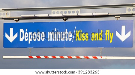A French airport sign indicating the way out and the passenger drop off point called 'Kiss and Fly' - stock photo