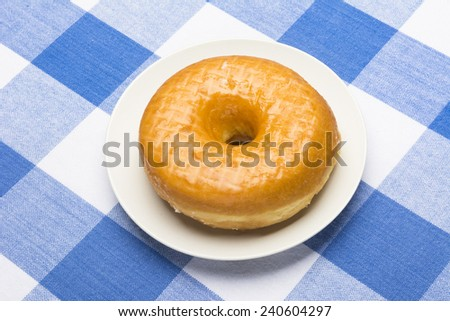 A fresh, delicious glazed donut on a classic, checkered diner tablecloth  - stock photo