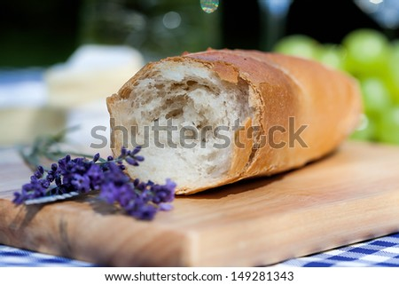 A fresh French baguette and a lavender piece - stock photo
