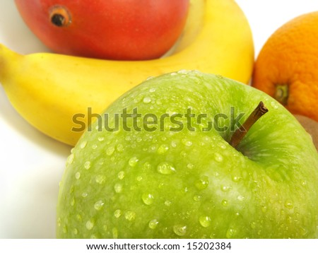 A fresh green apple with water drops and in the background a blurred mango, banana and orange - stock photo