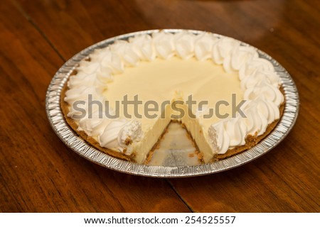 A fresh lemon meringue or key lime pie on a wood table - stock photo