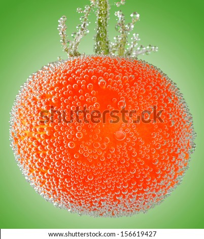 A fresh organic tomato immersed in mineral water on green background - stock photo
