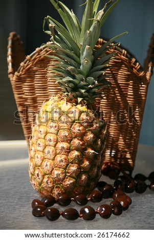 a fresh picked pineapple with a Kukui Nut Lei against a wicker basket - stock photo