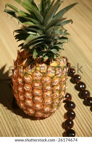 "a fresh pineapple with a ""KUKUI NUT LEI"" on a bamboo mat - stock photo"