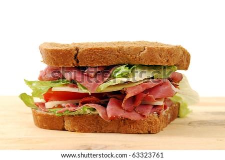 A fresh roast beef sandwich on a cutting board - stock photo