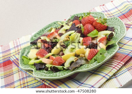 A fresh spring fruit salad with cranberries and nuts and a vinaigrette dressing, horizontal with copy space - stock photo