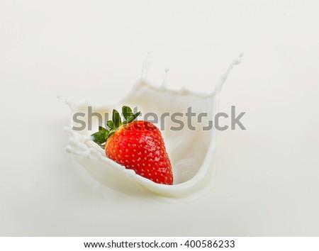 A fresh strawberry dropping and splash milk - stock photo