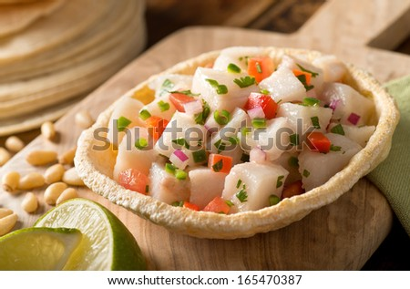 A freshly made white fish ceviche with tomato, red onion, cilantro, red pepper, lime, and serrano pepper. - stock photo