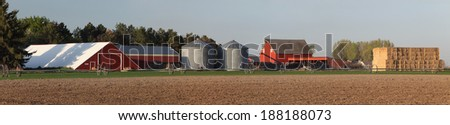 A freshly planted wheat field with irrigation equipment, and farm buildings in the background - stock photo