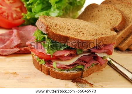 A freshly prepared roast beef and swiss cheese sandwich - stock photo